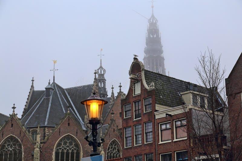 Gammal kyrka och historiska hus i Amsterdam arkivbild