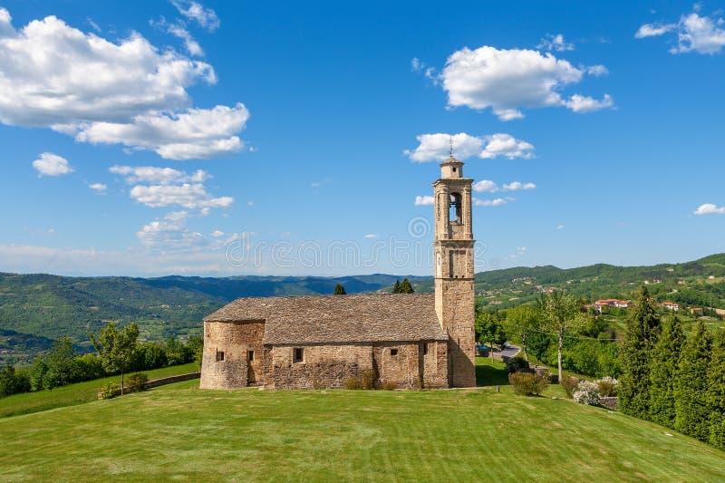 Gammal kyrka på grön gräsmatta i Italien royaltyfria foton