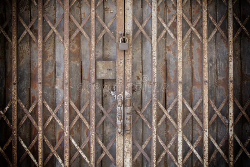 Gammal låst hopfällbar rostad ståldörr royaltyfri fotografi