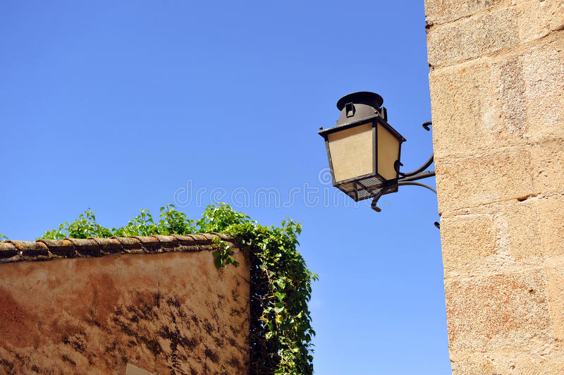 Gammal lampa i hörnet av en gata, monumental stad av Caceres, Extremadura, Spanien arkivbild