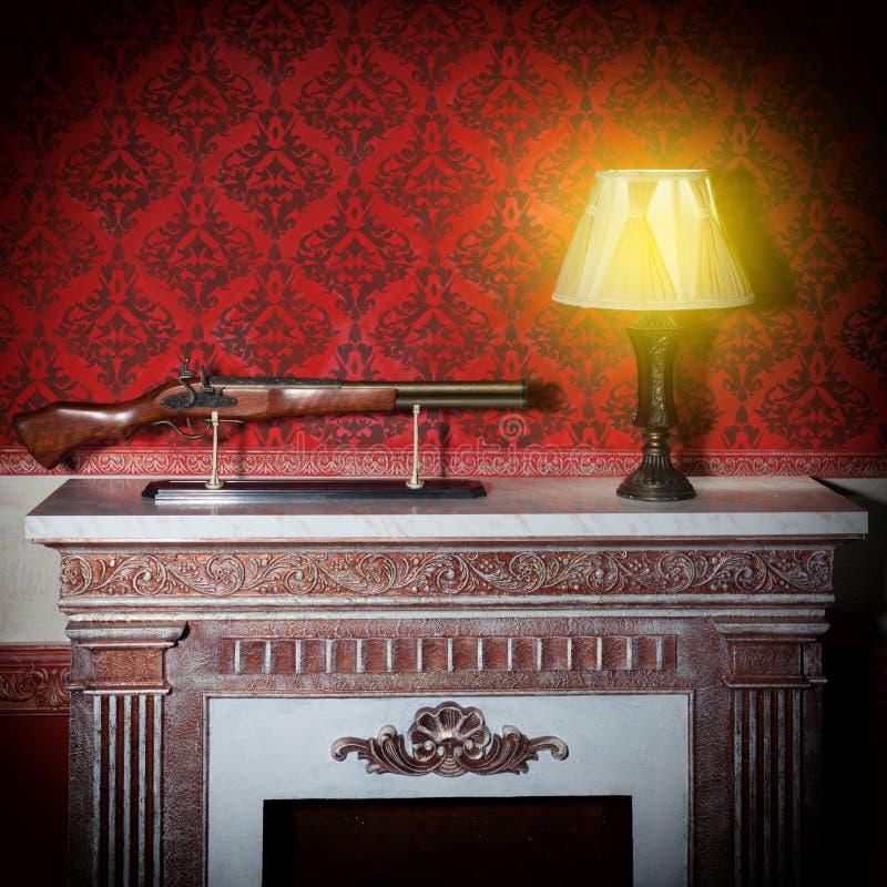 Gammal lampa och ett vapen i röd tappninginre royaltyfria foton