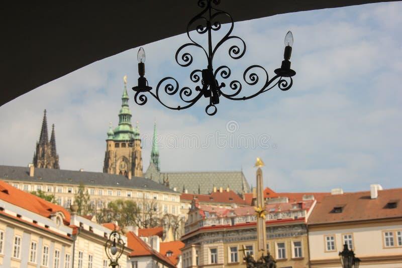 Gammal lampljusstake i mörk båge på bakgrund av sikten för Prague slott i Mala Strana royaltyfria foton