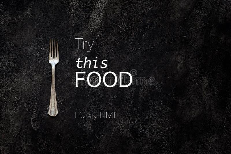 Gammal lantgårdgaffel med textförsök denna mat på konkret bästa sikt arkivbild