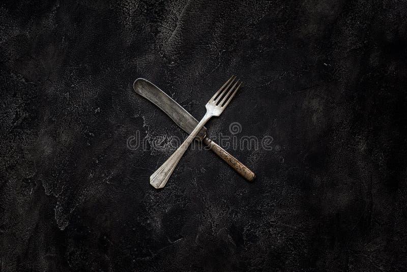 Gammal lantgårdkniv och gaffel X på konkret bästa sikt arkivfoto