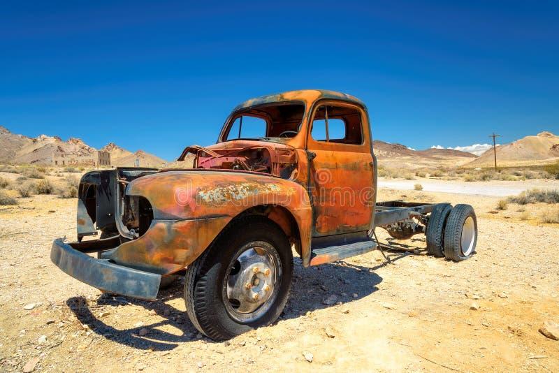Gammal lantgårdlastbil som lämnas i spökstad i öknen royaltyfria bilder