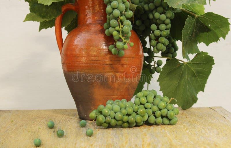 Gammal lantlig kanna med gröna druvor och druvasidor på en träbakgrundscloseup arkivfoton