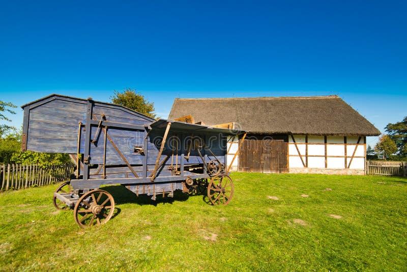 Gammal lantlig ladugård i det Polen och tröska-maskin XIXth århundradet royaltyfri bild