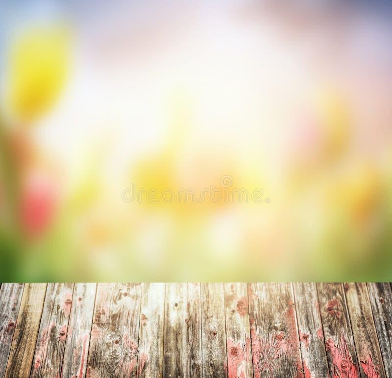 Gammal lantlig trätabell över suddig bakgrund för blommaträdgård royaltyfria bilder