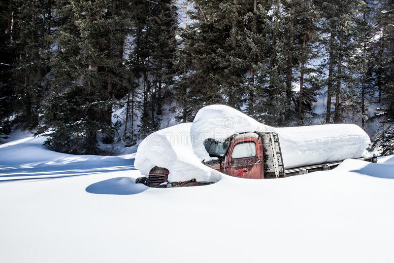 Gammal lastbil som begravas i den djupa snön royaltyfria foton