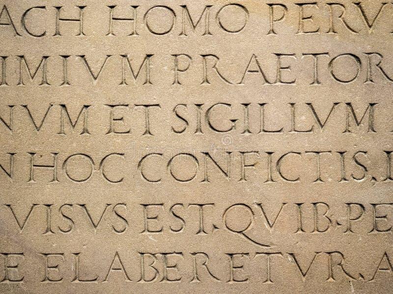 Gammal latinsk text som inristas på stenen arkivfoton