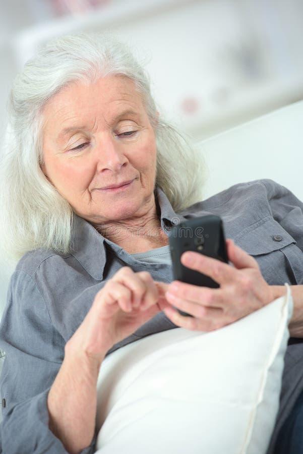 Gammal le kvinna med mobiltelefonen arkivbilder