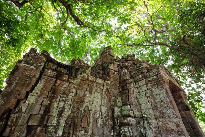 Gammal liten slott som täckas med kokt trä av den Bayon templet på Angkor Thom arkivfoton