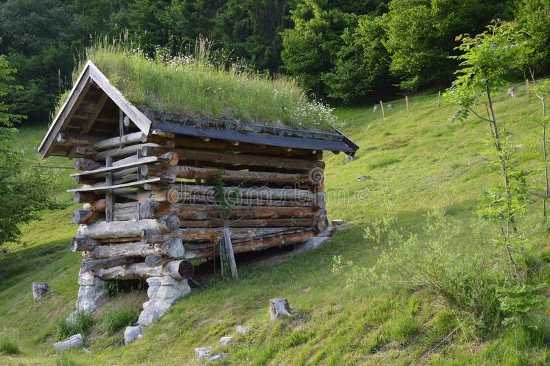 Gammal liten träladugård på de österrikiska fjällängarna arkivfoton