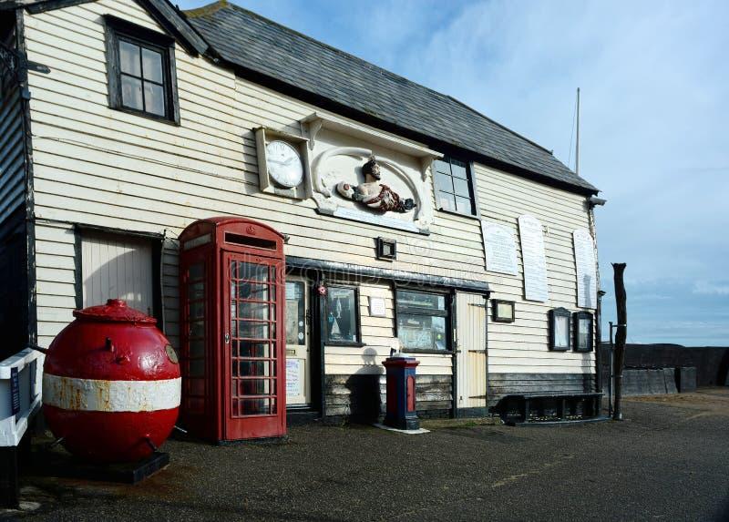 Gammal livräddningsbåtstation, röd telefonask och WWII-min arkivfoton
