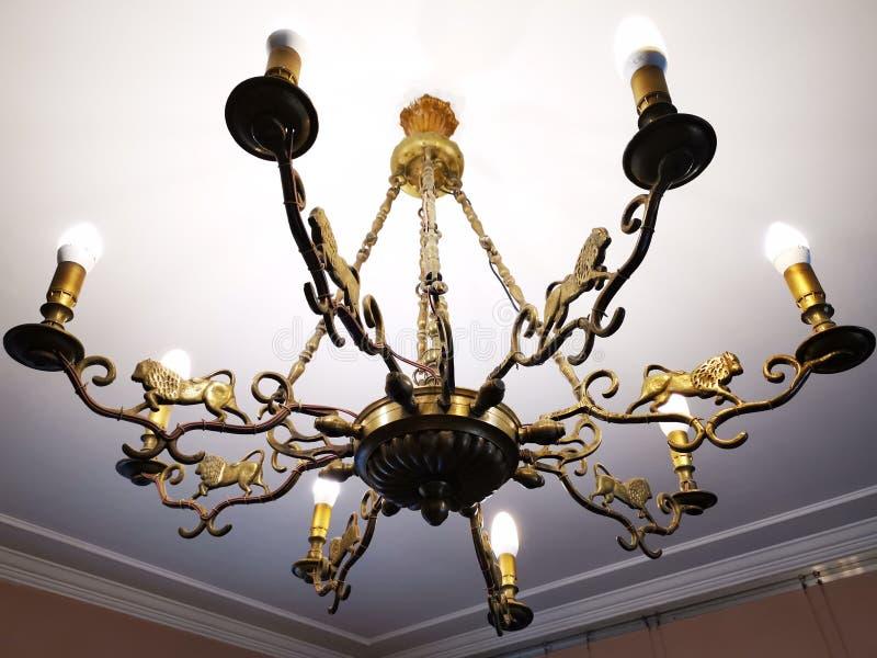Gammal ljuskrona av brons med åtta armar royaltyfria bilder