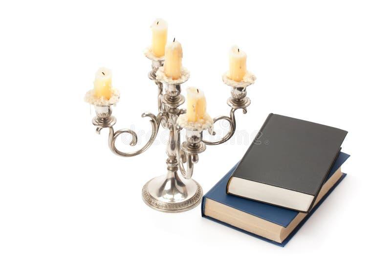 Gammal ljusstake med stearinljus och boken royaltyfri fotografi