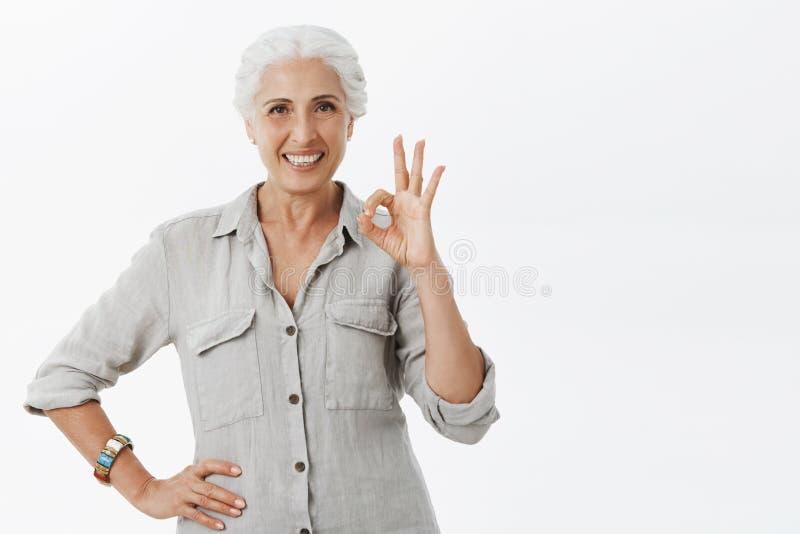 Gammal lycklig dam som försäkrar hennes pengar i säkert ställe tack vare banken Stående av nöjd säker och förtjust gullig åldring royaltyfri fotografi