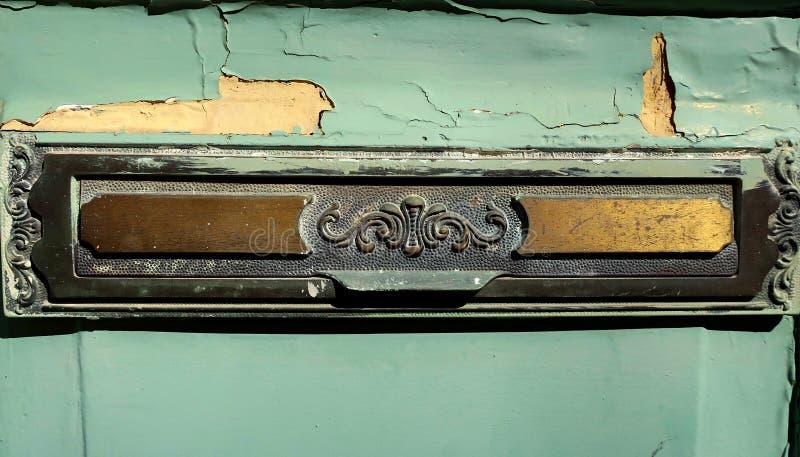 Gammal mässingspostbrevlåda på ytterdörr arkivbilder