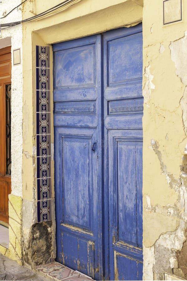 Gammal målad blå dörr av red ut trä och keramiska tegelplattor på en gammal murbrukvägg i Spanien royaltyfria bilder