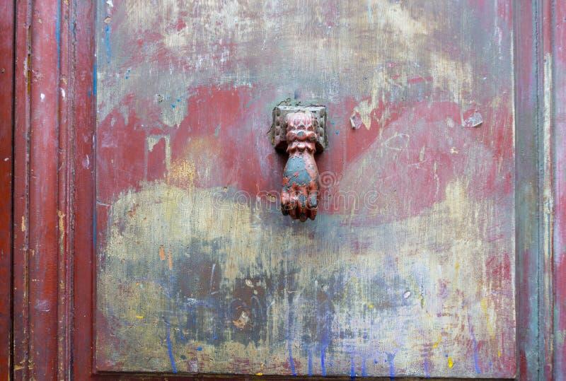 Gammal målarfärg suddade dörren med knackaren i form av den mänskliga handen i ce fotografering för bildbyråer