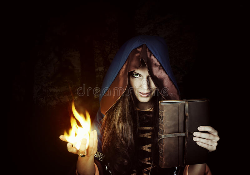 Gammal magisk bok för härlig ung halloween häxa royaltyfria foton