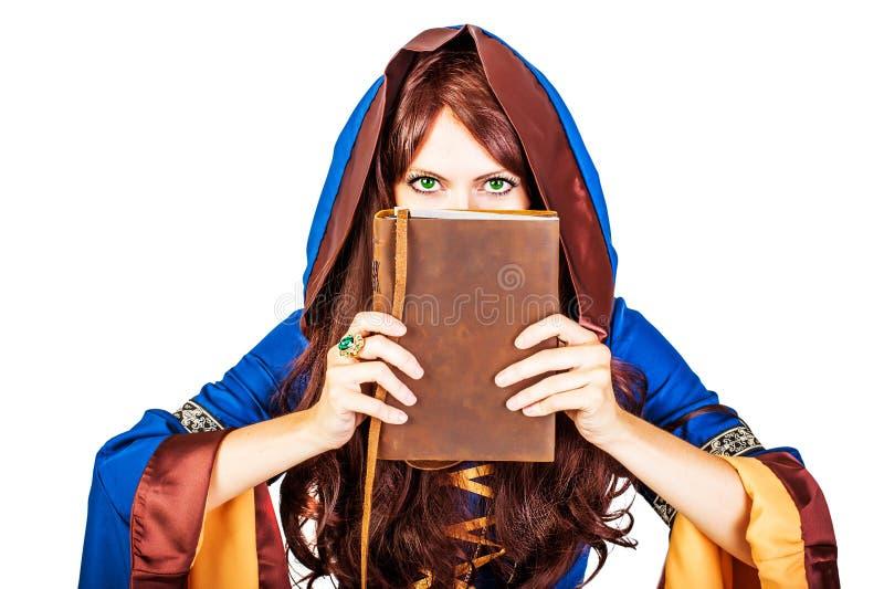 Gammal magisk bok för härlig ung halloween häxa på vit royaltyfria bilder