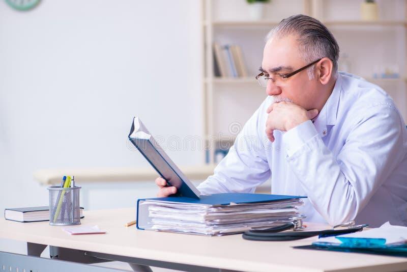 Gammal manlig doktor som arbetar i kliniken arkivfoto