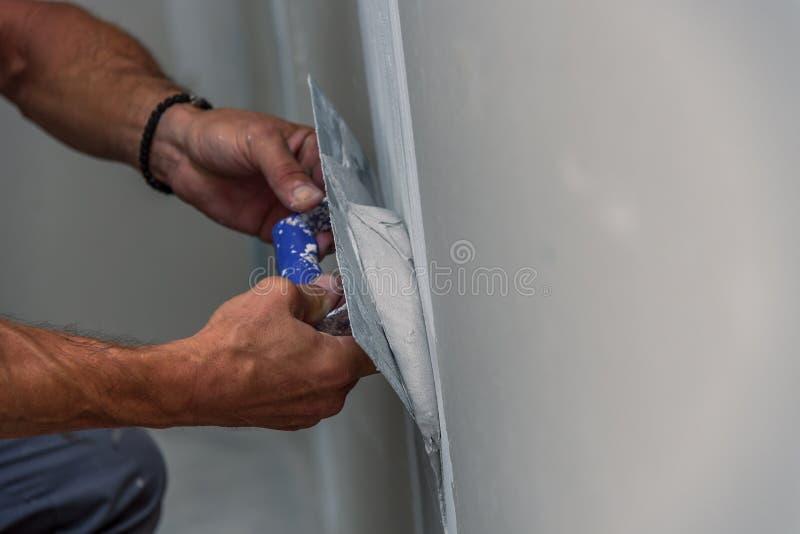 Gammal manuell arbetare med väggen som rappar hjälpmedel som renoverar huset arkivfoton