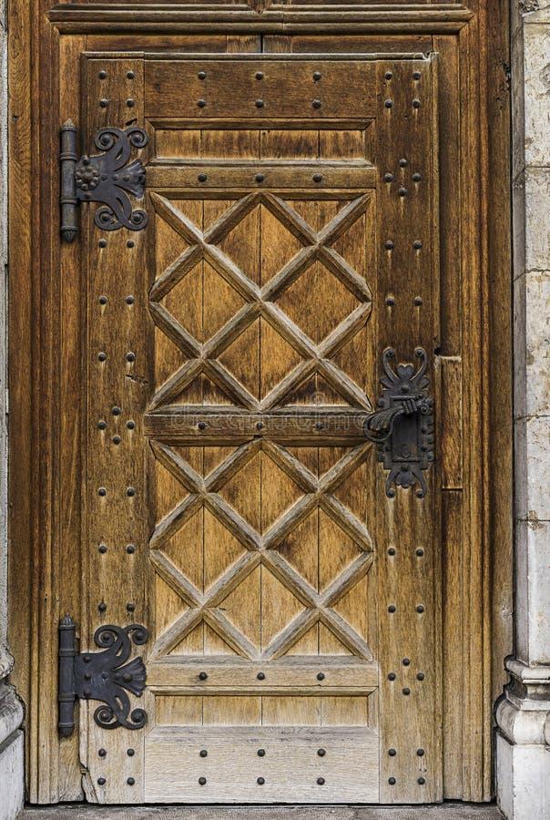 Gammal massiv dörr med ett stort metallhandtag arkivfoton