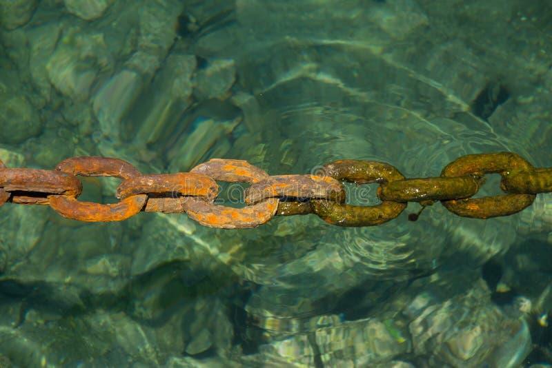 Gammal massiv rostig kedja som doppar in i klart havsvatten i hamn arkivfoton