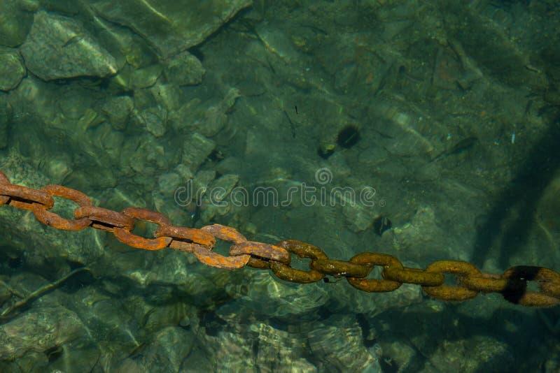 Gammal massiv rostig kedja som doppar in i klart havsvatten i hamn arkivbilder