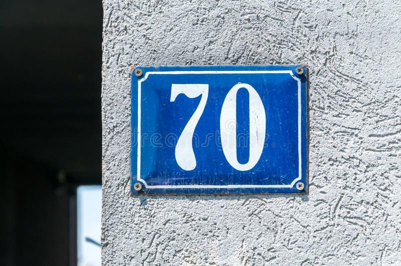 Gammal metall nummer 70 sjuttio för tappninghusadress på murbrukfasaden av den övergav yttre väggen för hem på gatasidan royaltyfri bild