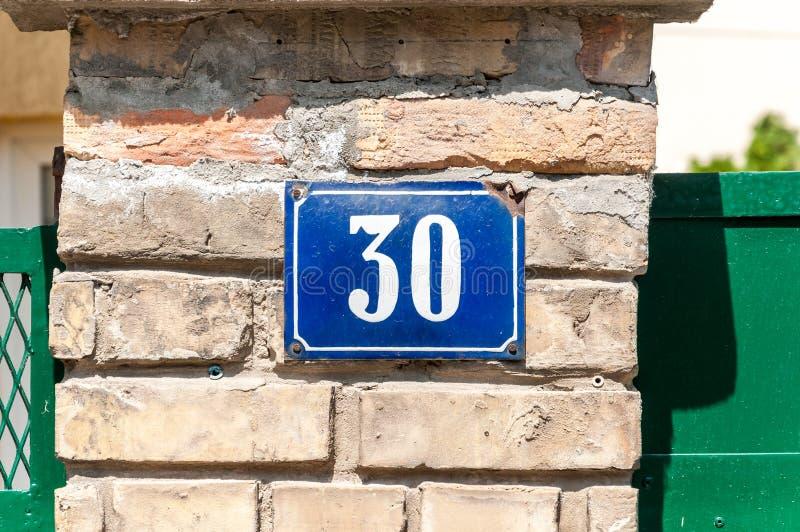 Gammal metall nummer 30 trettio för tappninghusadress på tegelstenfasaden av den övergav yttre väggen för hem på gatasidan arkivbilder