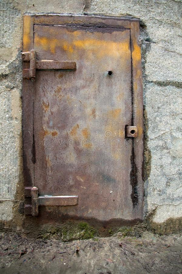 Gammal metalldörr i en betongvägg royaltyfri bild