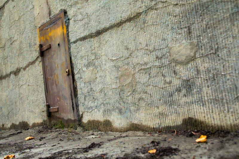 Gammal metalldörr i en betongvägg royaltyfria foton
