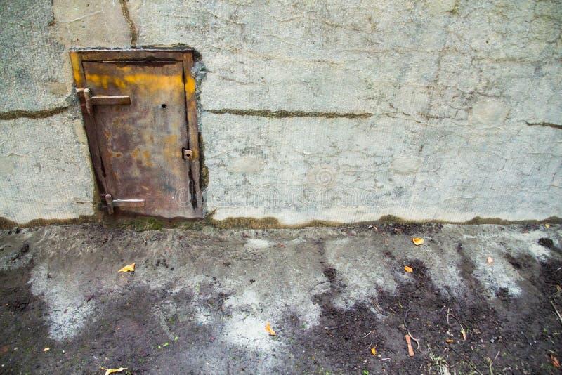 Gammal metalldörr i en betongvägg fotografering för bildbyråer