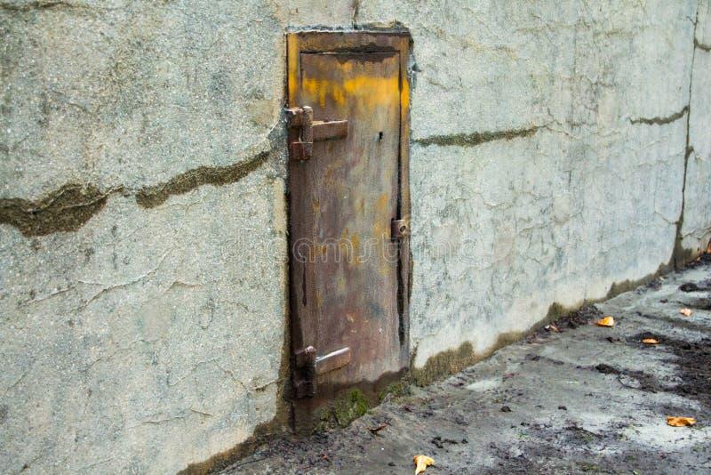 Gammal metalldörr i en betongvägg royaltyfria bilder