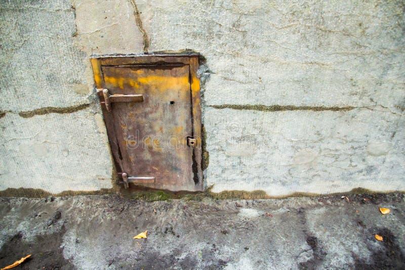 Gammal metalldörr i en betongvägg royaltyfri foto