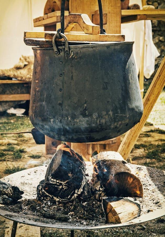 Gammal metallisk kokkärl på branden som lagar mat mat royaltyfria foton