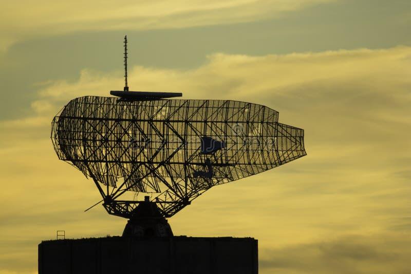 Gammal militär antenn för radiotorn på solnedgången royaltyfria bilder