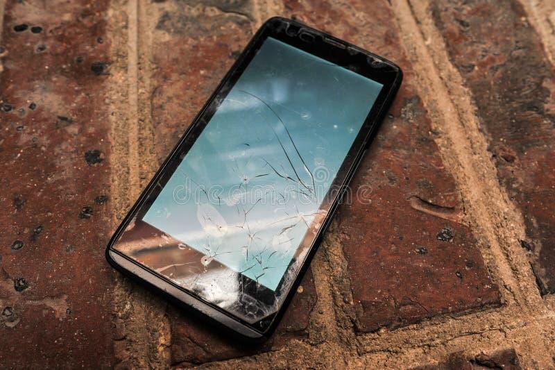 Gammal mobiltelefon (smartphone) med den brutna skärmen på en jordning royaltyfria foton