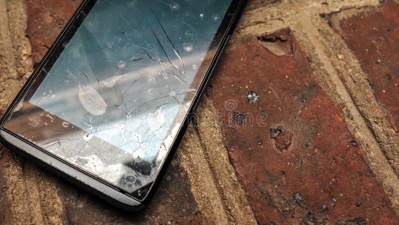 Gammal mobiltelefon (smartphone) med den brutna skärmen på en jordning royaltyfri bild