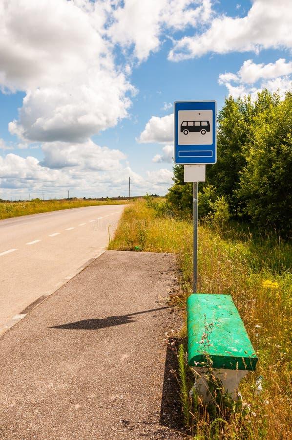 Gammal modehållplats med den målade gröna konkreta bänken på landsvägen som omges av den lantliga naturen, fält och växter arkivfoto