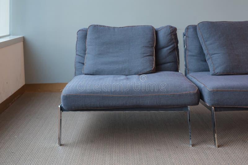 Gammal modern blåttstol på smutsigt mattgolv royaltyfri bild