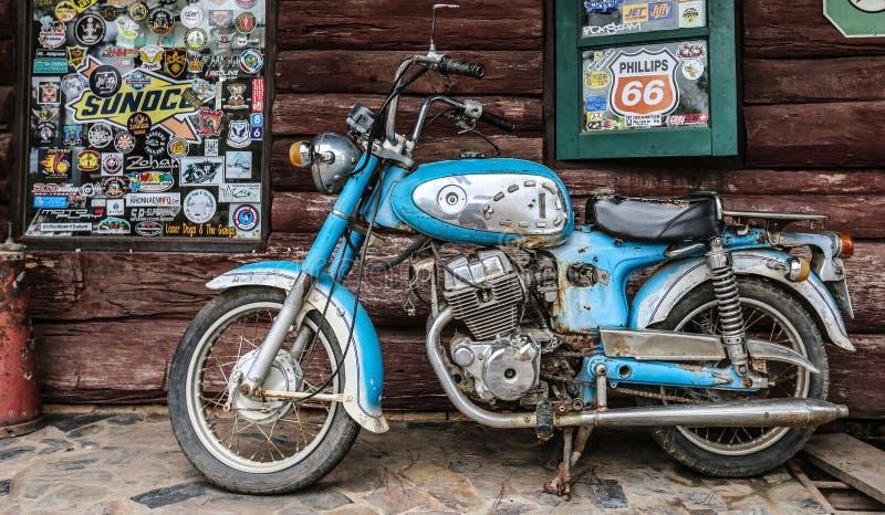 Gammal motorcykel på wood bakgrund, i Thailand royaltyfri bild