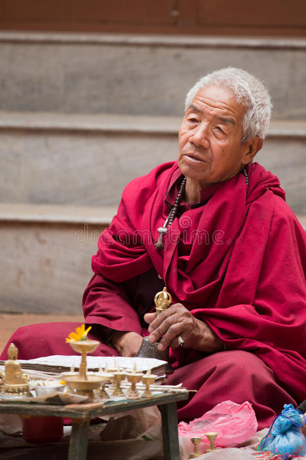Gammal munk som ber i Katmandu arkivbild