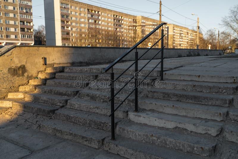 Gammal murken trappa som göras av betong i ett gammalt sovjetiskt område i Riga, Lettland royaltyfri foto