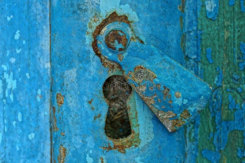 gammal nyckelhål för metall på en sliten trädörr arkivfoto