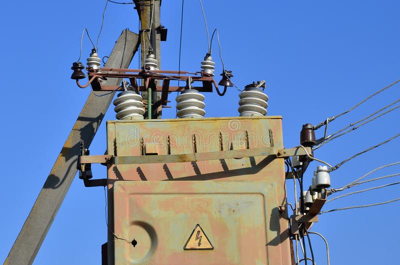 Gammal och föråldrad elektrisk transformator mot bakgrunden av en molnfri blå himmel Apparat för fördelning av tillförsel av höjd royaltyfri bild