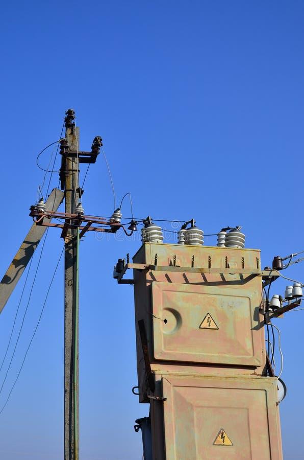 Gammal och föråldrad elektrisk transformator mot bakgrunden av en molnfri blå himmel Apparat för fördelning av tillförsel av höjd arkivbilder